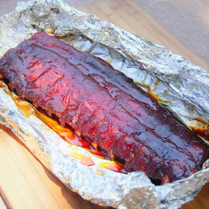 Partially finished rack of glazed pork ribs sitting in foil.