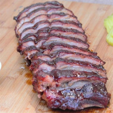 Finished glazed pork ribs sliced and displayed in a row on a wooden cutting board.