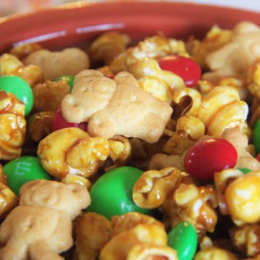 Close-up of celebration popcorn with caramel popcorn, tiny teddy cookies and red and green M&M's for a Christmas theme.