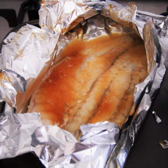 Fish filet resting in open foil pouch with wine, chilli sauce and butter, ready to cook.