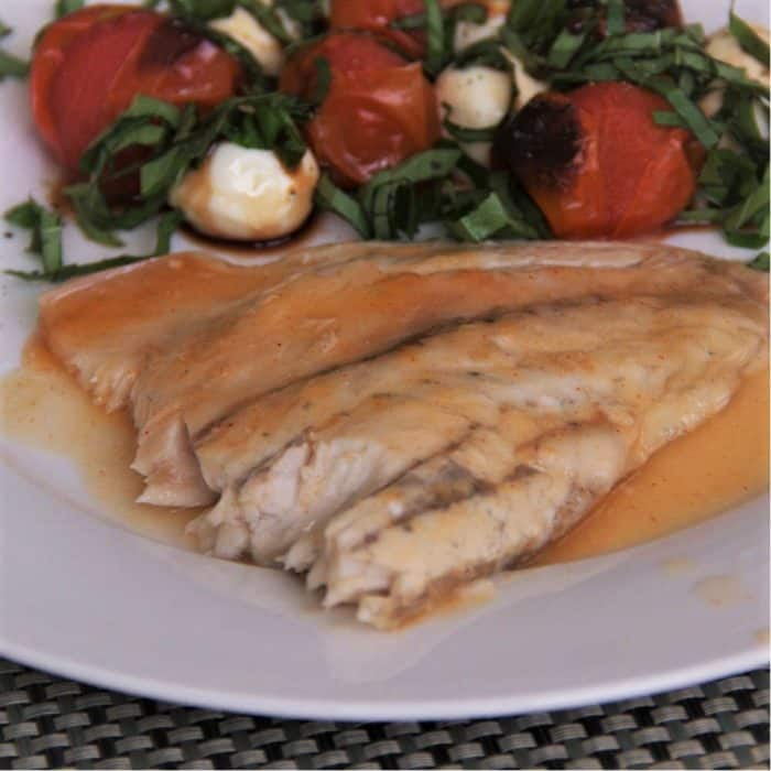 Completed fish filet resting in its cooking juices on a white plate next to caprese salad with tomato, basil and mozzarella.