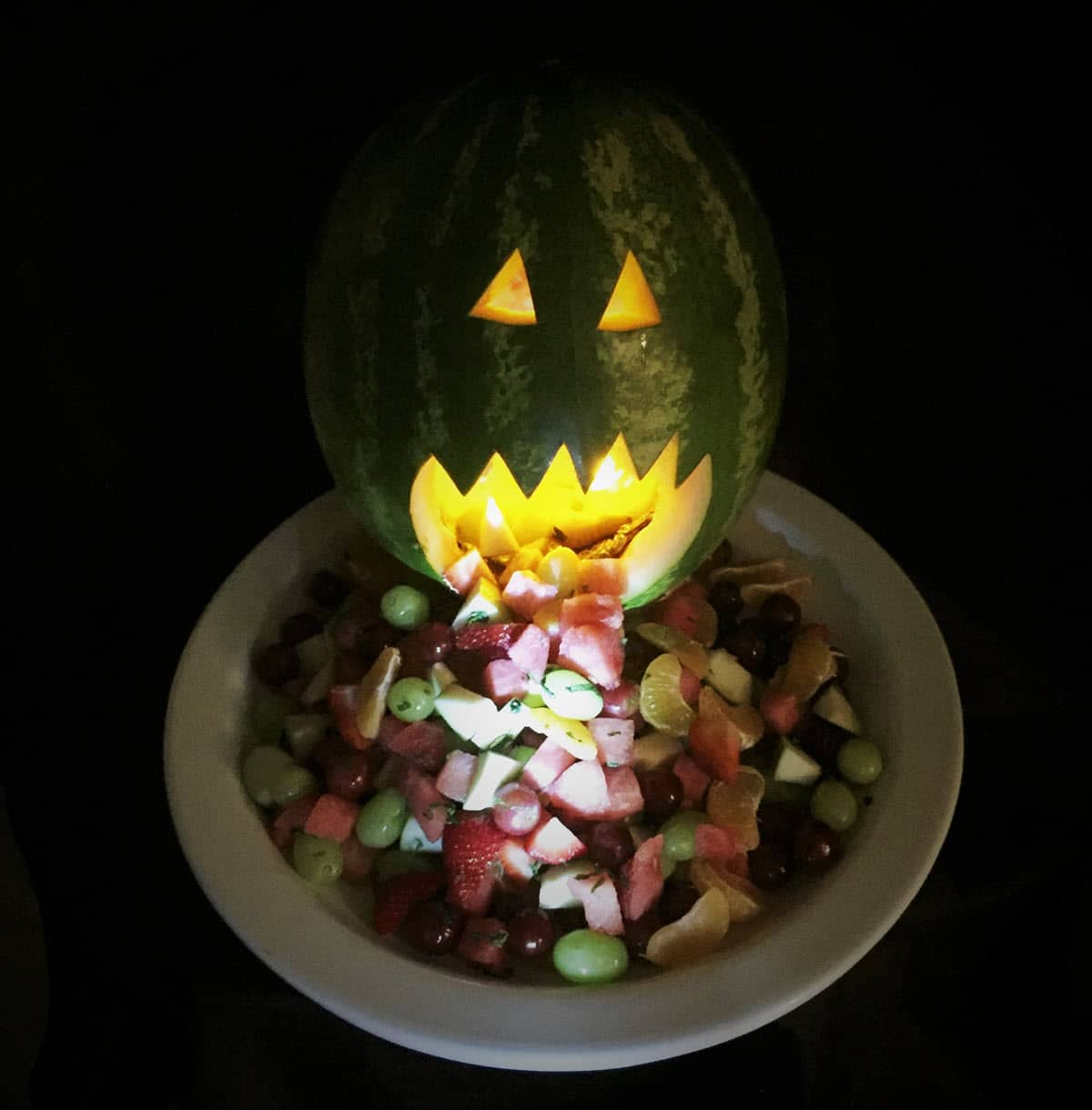 Watermelon jack-o-lantern in the dark, light from inside it is shining on fruit spilling out its mouth and down a platter.