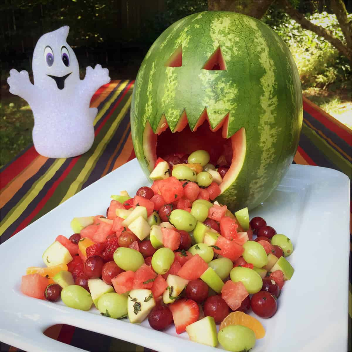Carved watermelon jack-o-lantern resting upright on a large plate with fruit spilling out its mouth and down the plate.