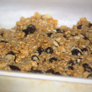 Close up of chunky muesli bar mix in a baking tray ready to gently flatten and bake.