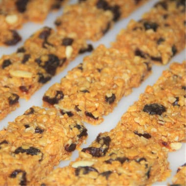 Several fully baked muesli bars sliced and resting on baking parchment.