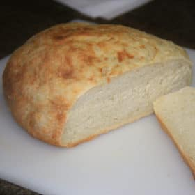 Fully baked round, domed cob loaf of bread with a browned top, loaf partially sliced to reveal an evenly baked crumb.