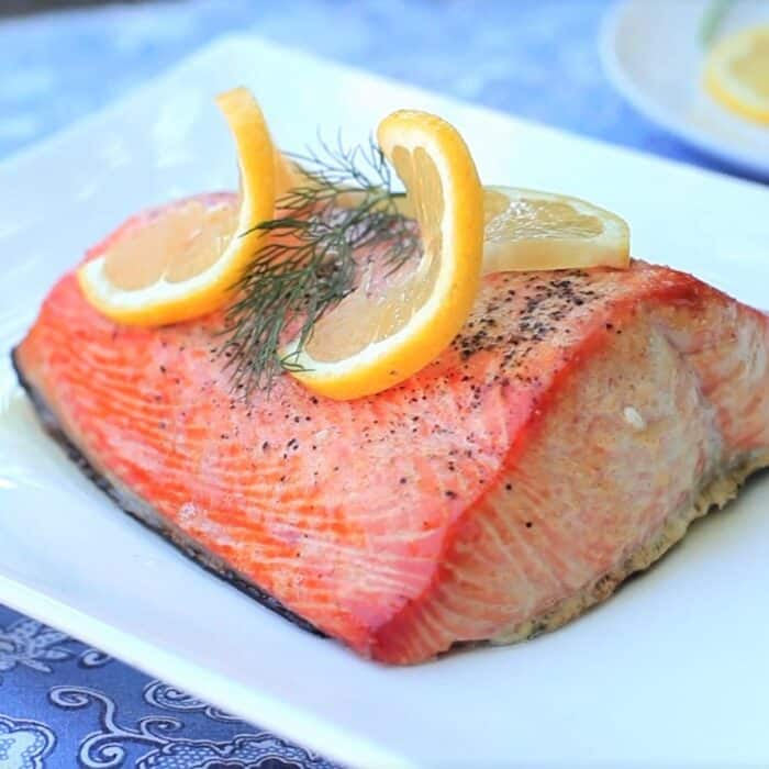 Cooked salmon filet garnished with two thin, twirled lemon slices and a dill sprig resting skin down on a white platter.