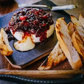 Smoked brie wheel oozing melted cheese, topped and dripping with chunky cranberry chutney, resting on a serving platter next to slices of toasted bread.