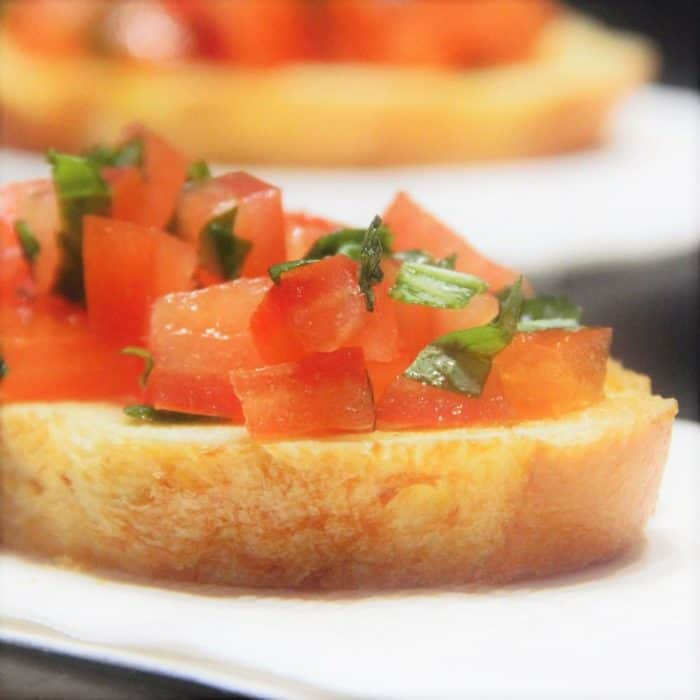Close up of a slice of baguette bread topped with diced tomato and fresh basil on a white napkin.