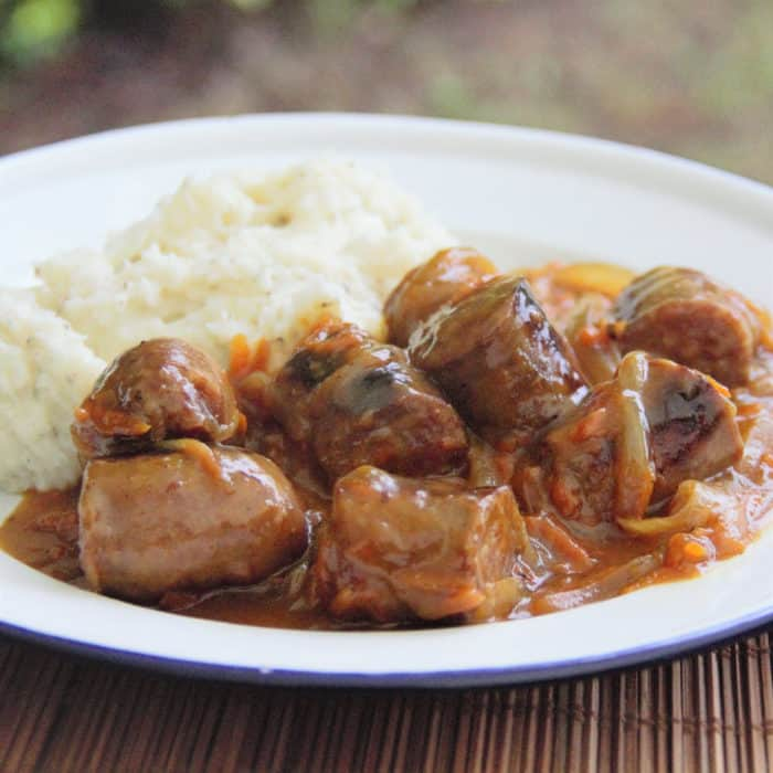 Completed curried sausages ready to serve on a white plate with a side of mashed potatoes.
