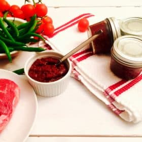 A ramekin of harissa ready to use, sitting next to a raw beef steak, green beans, and three small jars of canned harissa.