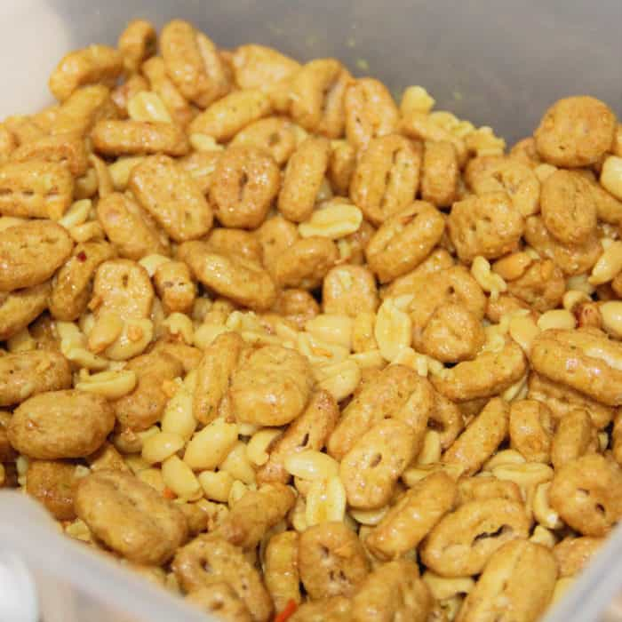 Close up of finished nuts and bolts mix, peanuts and cereal coated in savory flavored oil.
