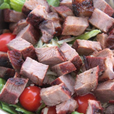 Close up of barbecued steak pieces on a salad of sliced lettuce, cherry tomatoes and shredded cheese.