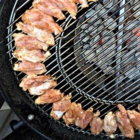 Seasoned chicken spare ribs in a curved row cooking via indirect heat along the outer edge of a grill over hot coals.
