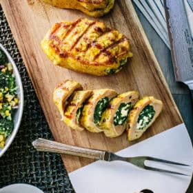Grilled pork chops resting on a wood cutting board, with one chop sliced into sections to show the spinach and feta stuffing.