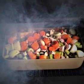 Chopped vegetables and wine covering Lamb shanks in an uncovered baking dish sitting in a smoker, ready to cook.