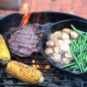 Steak, corn on the cob, and a cast iron skillet containing green beans and scallops, all cooking on a grill over hot coals.