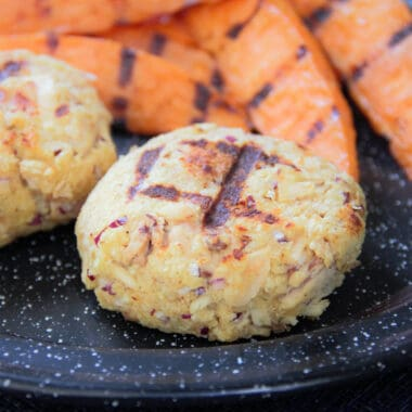 A black camp plate with two crab cakes and a side of sweet potato wedges