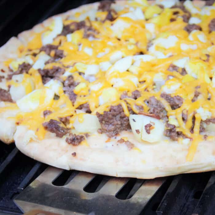 The breakfast pizza being rotated on the grill