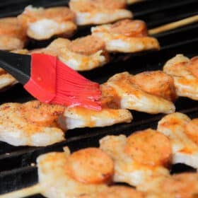 Looking accross shimp and smoked sausage skewers on a grill while they are being glazed with a red brush.