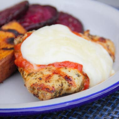 A white camp plate with grilled chicken parma and a side of sweet potato and beetroot.