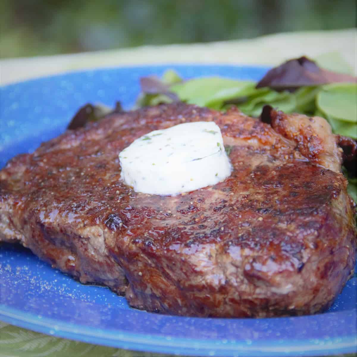 Three pepper steak is served with a slice of the compound butter