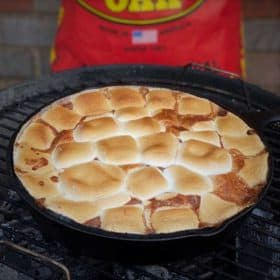 A finished easy chocolate s'mores pie still sitting in the barbecue.