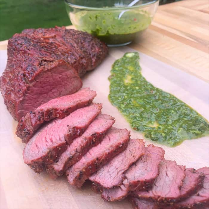 Thinly sliced tri tip is served with chimichurri sauce