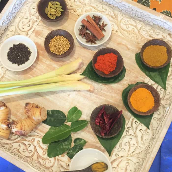 A range of herbs and spices laid out on a tray