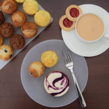 Areal photo down on a morning tea of cookies, mini muffins, and a cup of tea