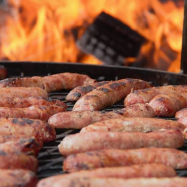 Sausages cooking on a live fire grill