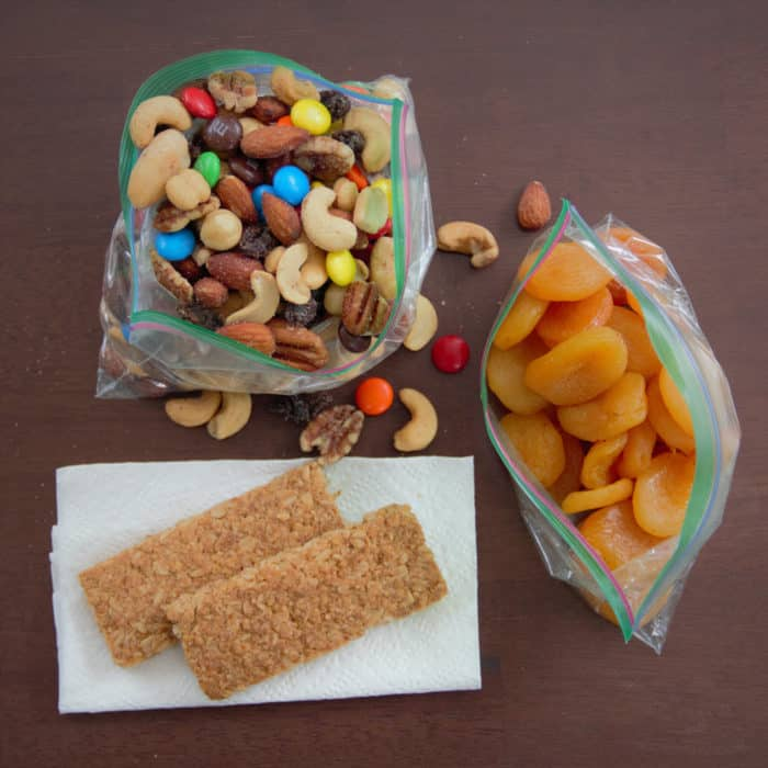 Areal photo of various snacks including dried fruit, trail mix, and muesli bars.