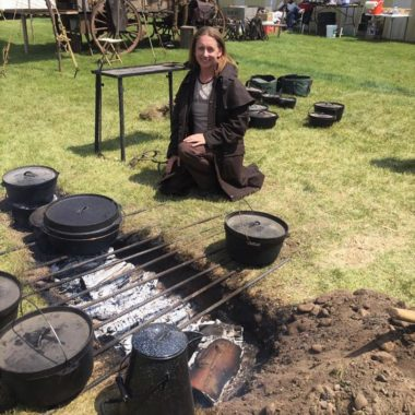 Saffron Hodgson sitting next to a trnch fire with multiple cast iron items around her
