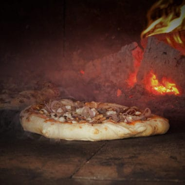 Pizza cooking in a traditional wood burning pizza oven