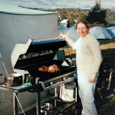 Saffron Hodgson opening a closed grill to expose the roast lamb and vegetables inside