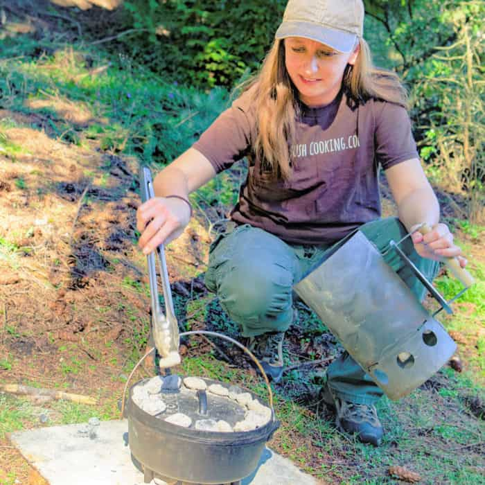 Saffron Hodgson Placing Charcoal onto a Dutch oven to bake its contents