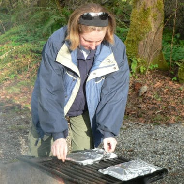 Saffron Hodgson Placing a foil packed of food on a campfire grate