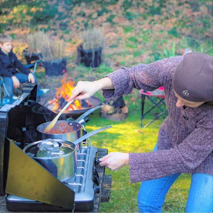 Saffron Hodgson adjusting the temperature of a portable gas stove.