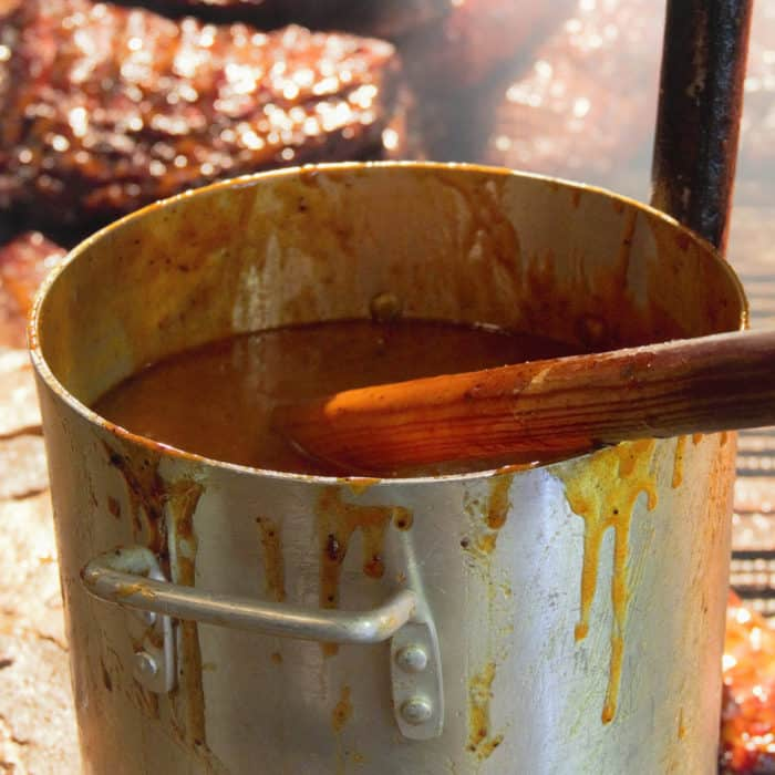Large pot of sauce with meat in the background