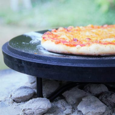 A ham pizza is sitting on a Dutch oven lid over coals after being cooked awaiting to be moved and served.