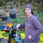 Portrait Photo of Saffron Hodgson cooking on a Camp Stove with a campfire in the background