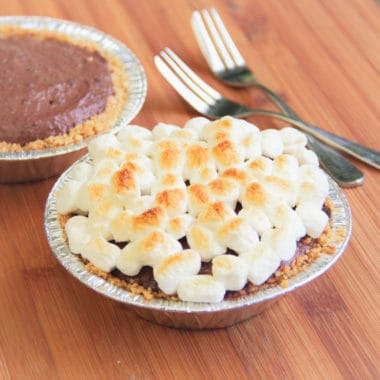 Two camp s'more tarts one with brown marshmallows, the other yet to have the marshmallows added.