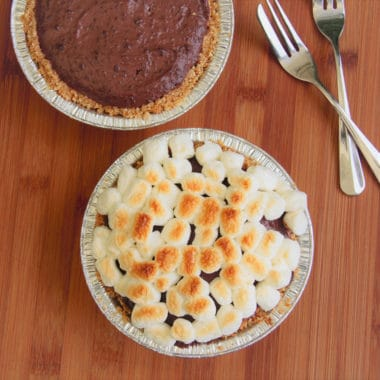 Looking down at two tarts, one with a browned marshmallow top the other just a chocolate tart without any marshmallows.