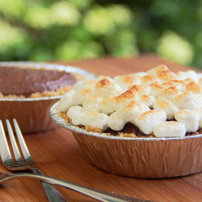 A finished s'more tart topped with browned marshmallows with a partly completed one in the background.