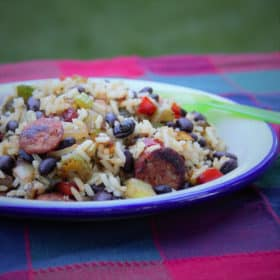 A plate of Smoked Sausage and Black Bean Rice served on a red patch picnic tablecloth