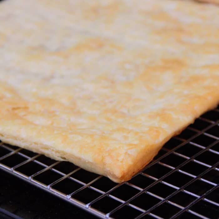 A golden brown sheet of cooked puff pastry sitting on a cooling rack.