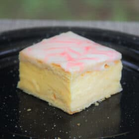 A single square slice of vanilla slice sitting on a black camp plate.