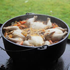 A large Dutch oven filled withe the orange wild rice with four Cornish game hens within it.