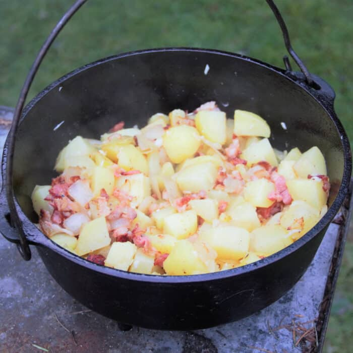 A Dutch oven sitting on concrete filled with bacon potatoes.