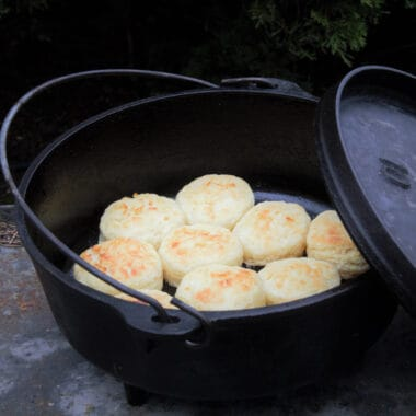 A Dutch oven with its lid off leaning on the main part is filled with golden brown cooked biscuits.